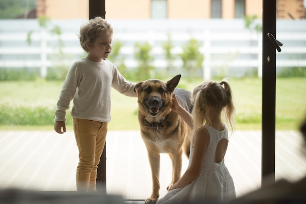 Children boy and girl playing with dog coming inside house Free Photo