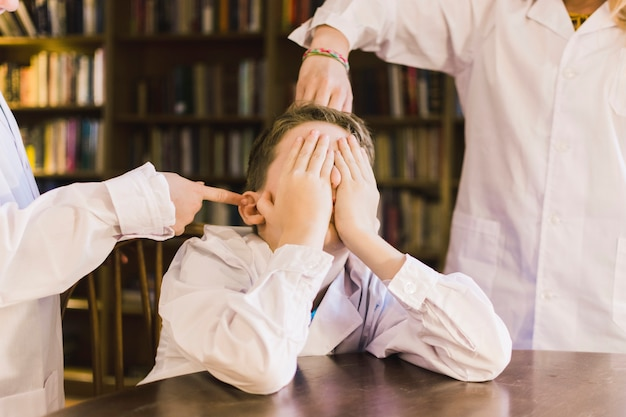 Children bullying little boy in library Free Photo