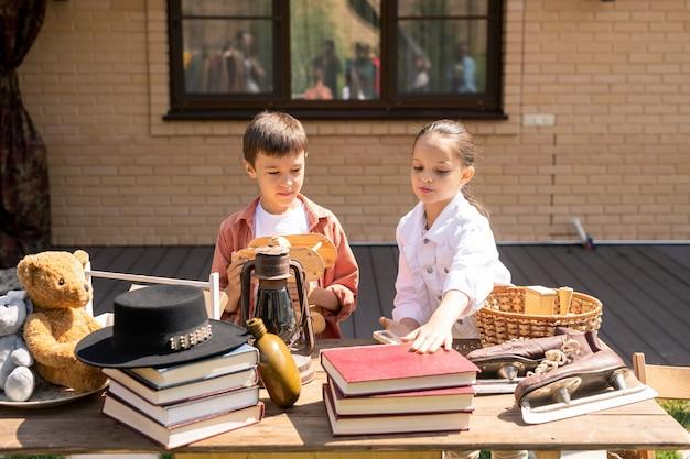 Children buying toy and book at garage sale Premium Photo