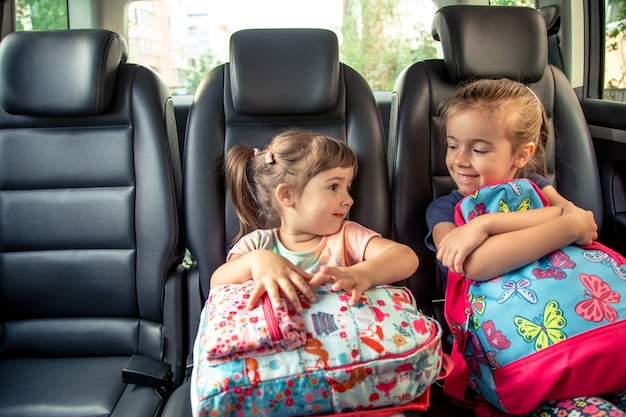 Children in the car go to school, happy, sweet faces of sisters Free Photo