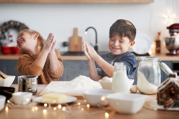 Дети сжимают муку во время выпечки печенья на рождество Бесплатные Фотографии