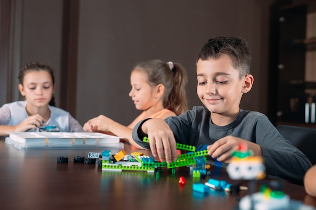 Children in the classroom collect figure from the designer. Premium Photo