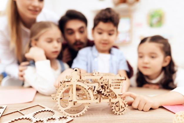 Children collect 3d puzzle - a tractor. Premium Photo