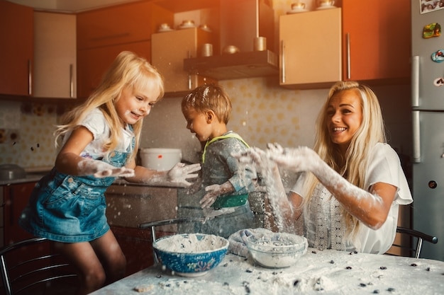 Children cooking with their mother and throwing flour Free Photo