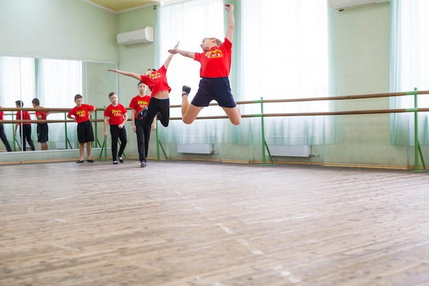 Children dance with a trainer in a large training room. Premium Photo