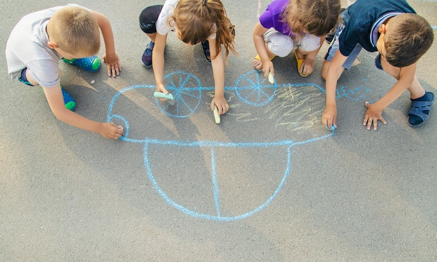 Children draw a car with chalk on the pavement Premium Photo