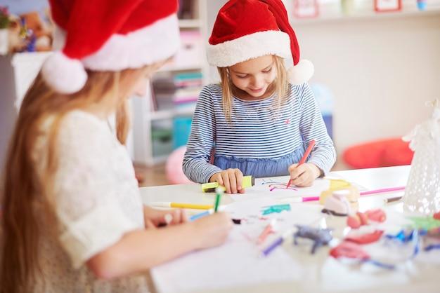 いくつかのクリスマスの絵を描く子供たち 無料写真