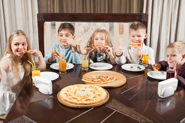 Children eat pizza in a restaurant. Premium Photo