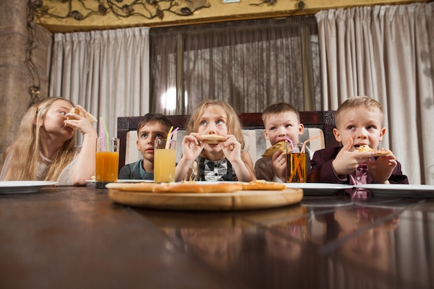 Children eat pizza in a restaurant. Premium Photo