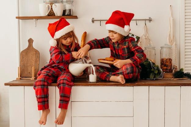 クリスマスのクッキーを食べて牛乳を飲む子供たち 無料写真