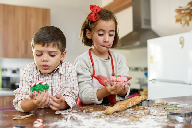 Children eating christmas cookies and cup cakes in the kitchen ...