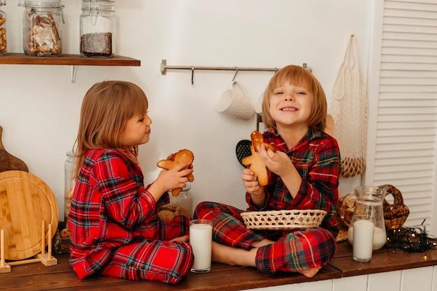Bambini che mangiano biscotti insieme il giorno di natale Foto Gratuite