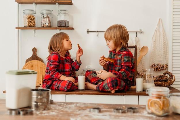 クリスマスの日に一緒にクッキーを食べる子供たち 無料写真