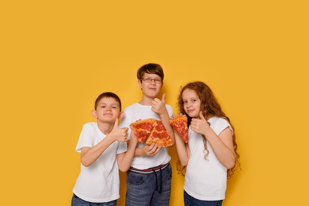 Children eating pepperony pizza on yellow background. unhealthy food concept. Premium Photo
