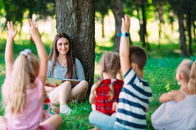 Children and education, young woman at work as educator reading book to boys and girls in park. Premium Photo