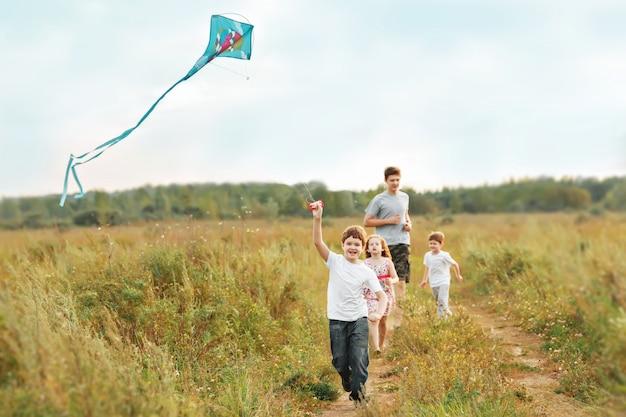 Children enjoy playing with a flying kite. Premium Photo