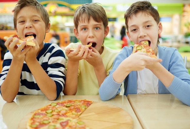 Children enjoying pizza Free Photo