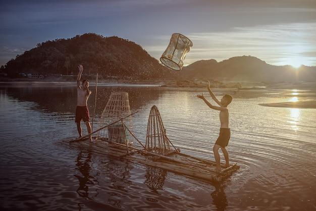 Children fisherman boy with catching fish on lake river thailand Premium Photo