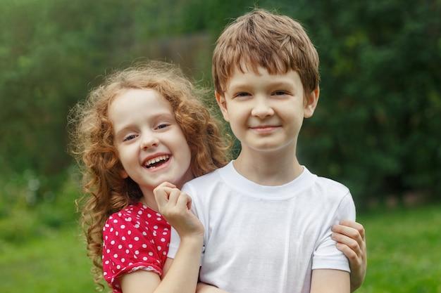 Children friends embracing in summer park. Premium Photo