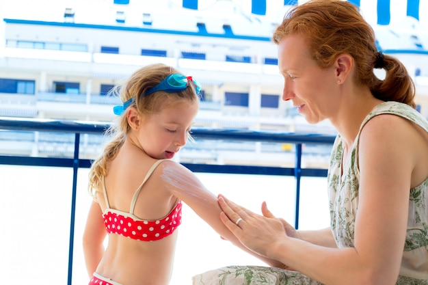 Children girl with mother applying sunscreen Premium Photo