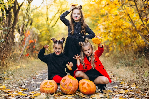 Children girls dressed in halloween costumes outdoors with pumpkins Free Photo