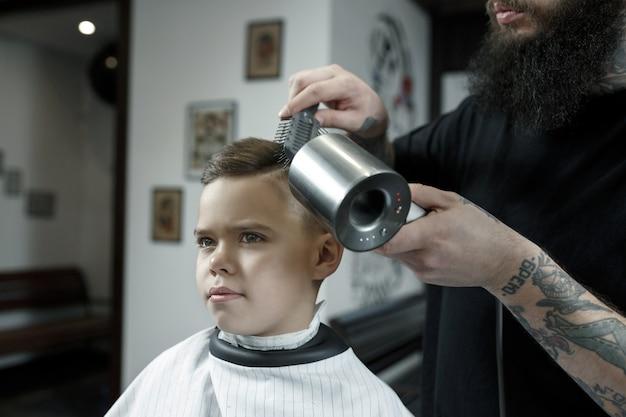 Детский парикмахер резки маленького мальчика на темном фоне. Бесплатные Фотографии