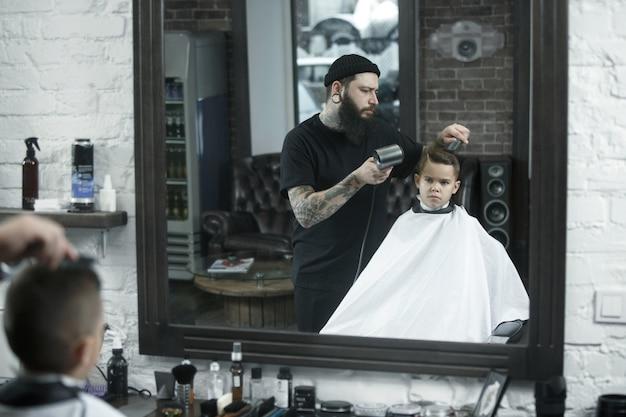 Детский парикмахер режет маленького мальчика на фоне темноты Бесплатные Фотографии