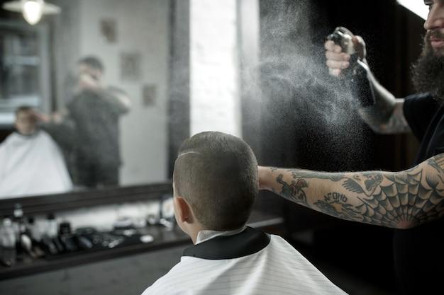 Parrucchiere di bambini che taglia ragazzino contro un'oscurità Foto Gratuite