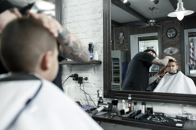 Parrucchiere di bambini taglio ragazzino in un negozio di barbiere Foto Gratuite