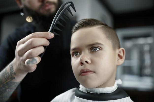 Детский парикмахер режет маленького мальчика в парикмахерской Бесплатные Фотографии