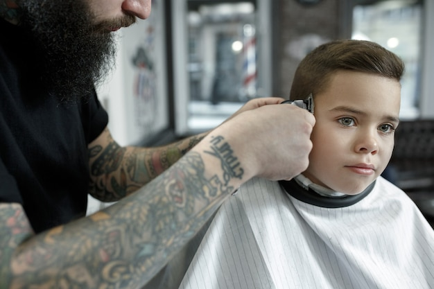 Children hairdresser cutting little boy Free Photo