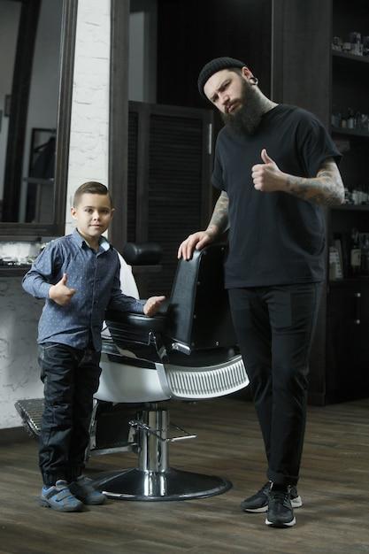 Parrucchiere di bambini e ragazzino contro uno sfondo scuro dopo il taglio di capelli. la mano del maestro ha un tatuaggio con la parola rasatura Foto Gratuite