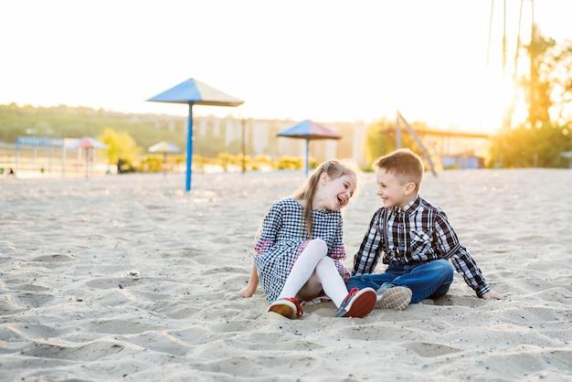 Children having fun on the beach. boy and girl lough Premium Photo