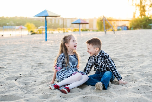 Children having fun on the beach in summer warm day. boy and girl are lough Premium Photo