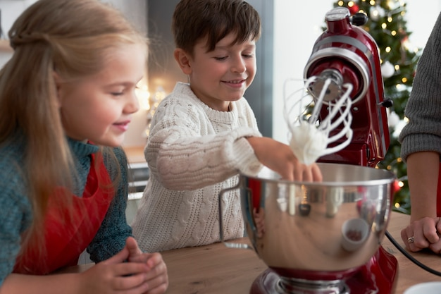 Bambini che aiutano la madre con la cottura di natale Foto Gratuite