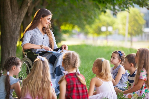 Children hold a lesson with the teacher in the park on a green lawn. Premium Photo