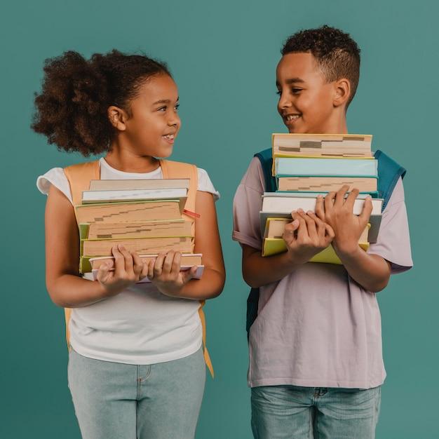 Bambini che tengono pile di libri Foto Gratuite