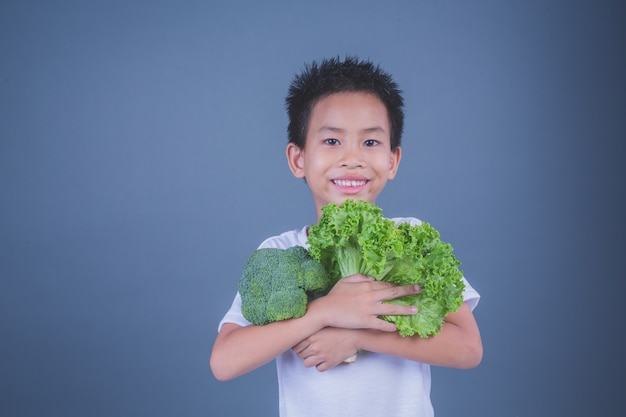Children holding vegetables on a gray background. Free Photo