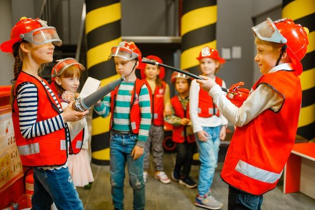 Дети в каске и униформе со шлангом и огнетушителем в руках играют в пожарного Premium Фотографии