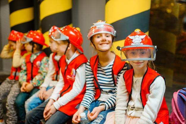 ヘルメットと制服を着た消防士の子供 Premium写真
