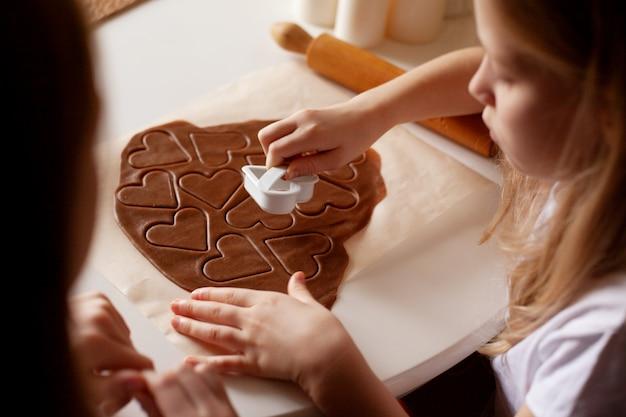 Дети на кухне делают домашнее печенье, вырезанное из теста в форме сердца Premium Фотографии