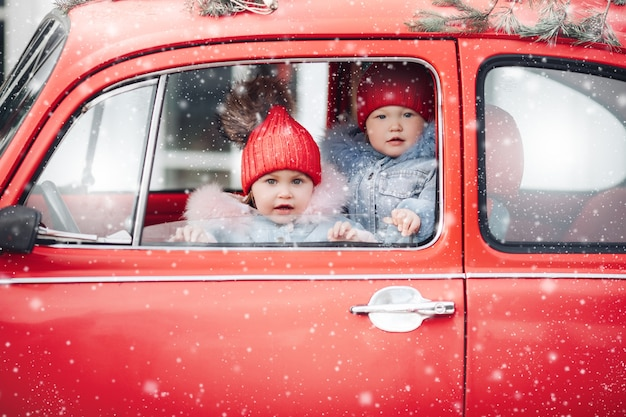 Дети в теплой одежде греются в красной машине во время снегопада Бесплатные Фотографии