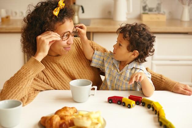 子供、子供、幸せな子供時代、家族の絆と子育ての概念。魅力的な若いヒスパニック系女性がktichenテーブルでコーヒーを飲み、幼い息子が眼鏡を外している間笑顔の写真 無料写真