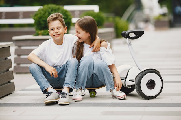 Children learn to ride hoverboard in a park on sunny summer day Free Photo