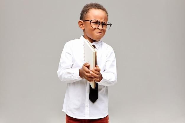 Bambini, apprendimento, istruzione e concetto di conoscenza. ritratto del ragazzino africano arrabbiato in camicia bianca, cravatta e occhiali, tenendo il quaderno e smorfie, arrabbiato perché non riesce a fare la matematica Foto Gratuite
