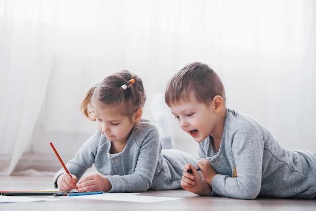 子供たちはパジャマ姿で床に横になり、鉛筆で描きます。鉛筆で描くかわいい子 Premium写真