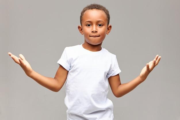 Bambini, stile di vita e linguaggio del corpo. colpo isolato del ragazzino afroamericano bello bello che ha sguardo fiducioso che morde il labbro inferiore e che fa il gesto con i palmi, mostrando che non ha paura Foto Gratuite