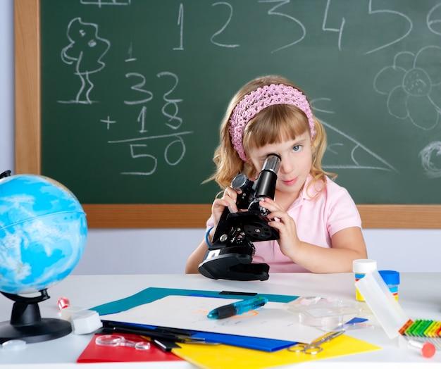 Children little girl at school classroom with microscope Premium Photo