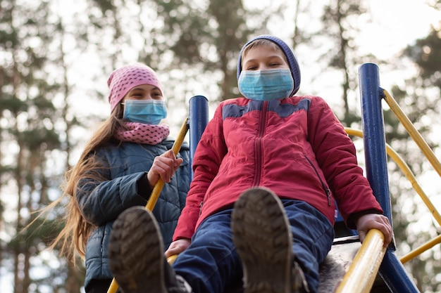 Children in medical masks on playground outdoor while coronavirus quarantine Premium Photo