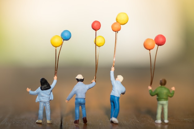 Children miniature figure with colorful balloons standing, walking and playing together on wooden table. Premium Photo